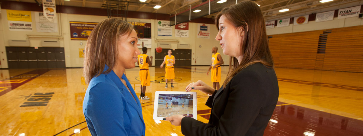 Teacher and student leaning from ipad in the gym