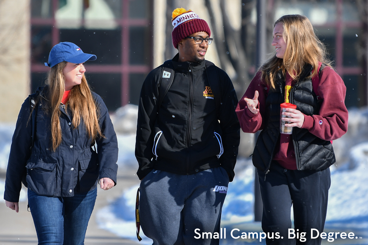 Three students walking in front of Sargeant Student Center outside during the winter talking with small snowflakes flying.
