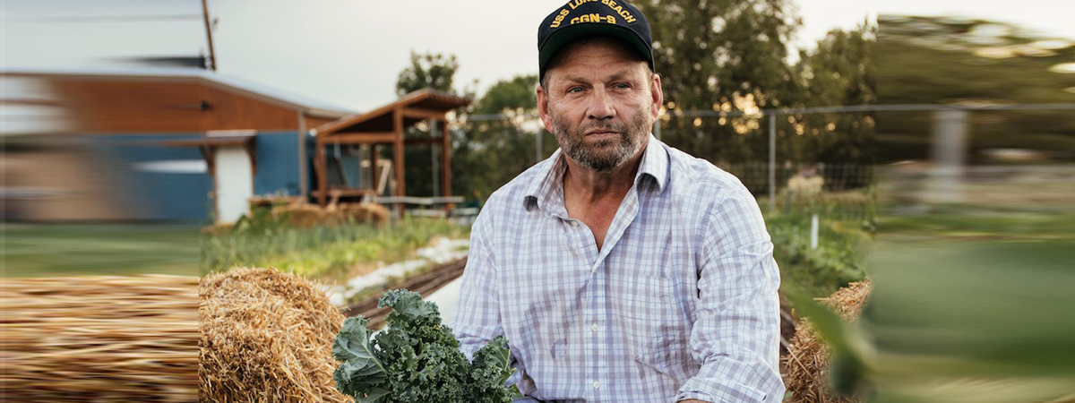 Veteran Farmer John Bauman on the farm with Kale